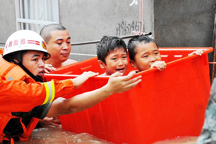 Bombeiro resgata crianças de enchente após a passagem do tufão Megi, em Ningde, na província chinesa de Fujian - 28/09/2016