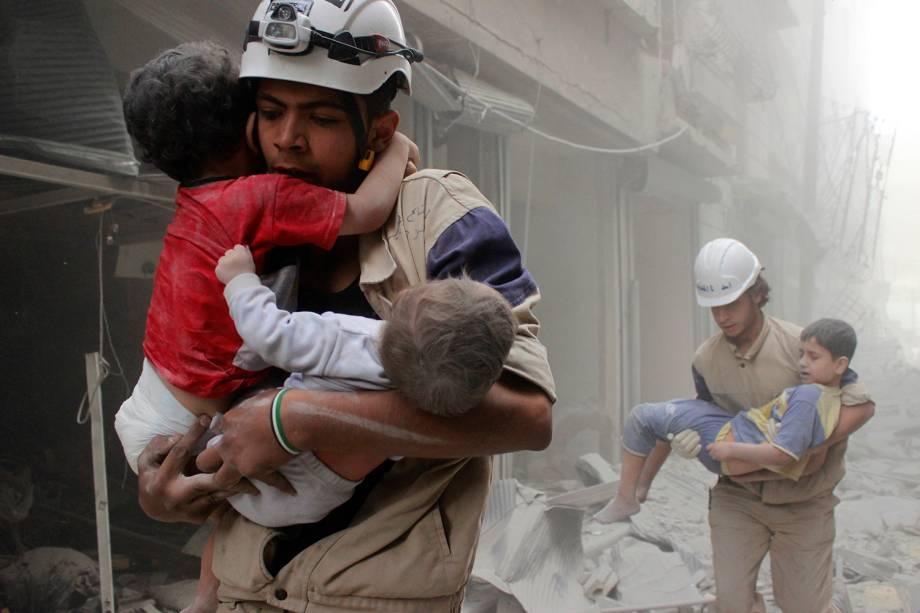 Membros da defesa civil resgatam crianças vítimas de um ataque aéreo que atingiu região vizinha a Alepo, na Síria - 16/09/2016