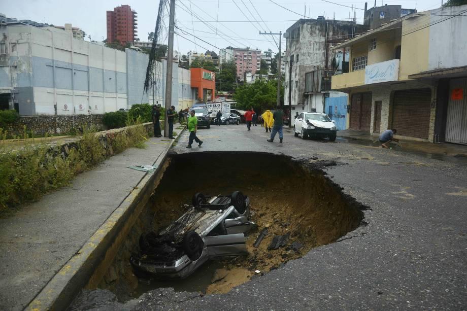 Carro é visto dentro de um buraco em uma estrada após fortes chuvas que causaram inundações em Campestre La Laguna, Acapulco, no México - 04/09/2016
