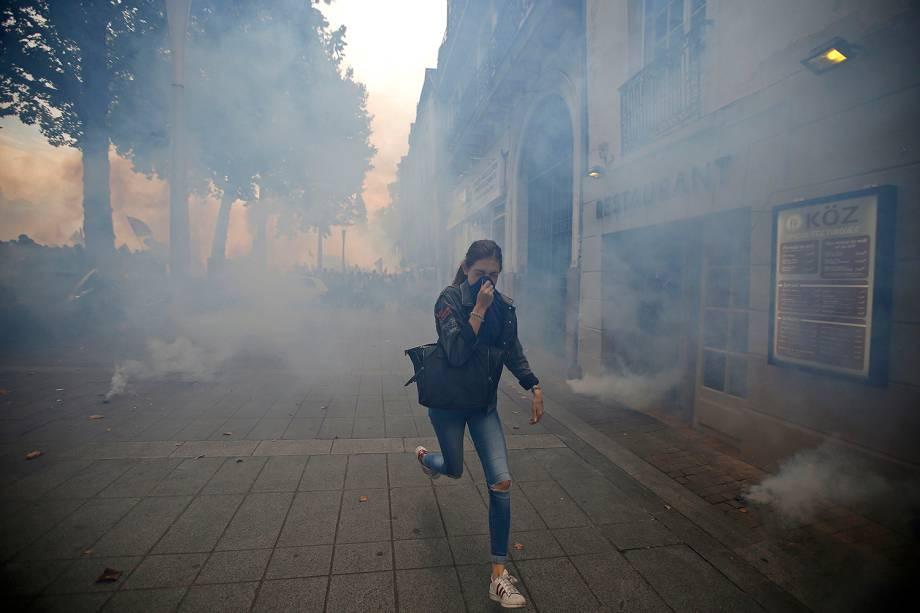 Mulher corre cobrindo o rosto para se proteger das bombas de gás lacrimogêneo disparadas pela polícia francesa durante protesto contra reforma nas leis trabalhistas, em Nantes, na França - 15/09/2016