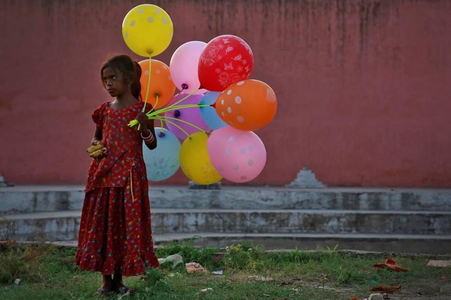 Garota vende balões, próximo ao rio Yamuna, durante festival religioso indiano em homenagem ao lorde Ganesha - 15/09/2016