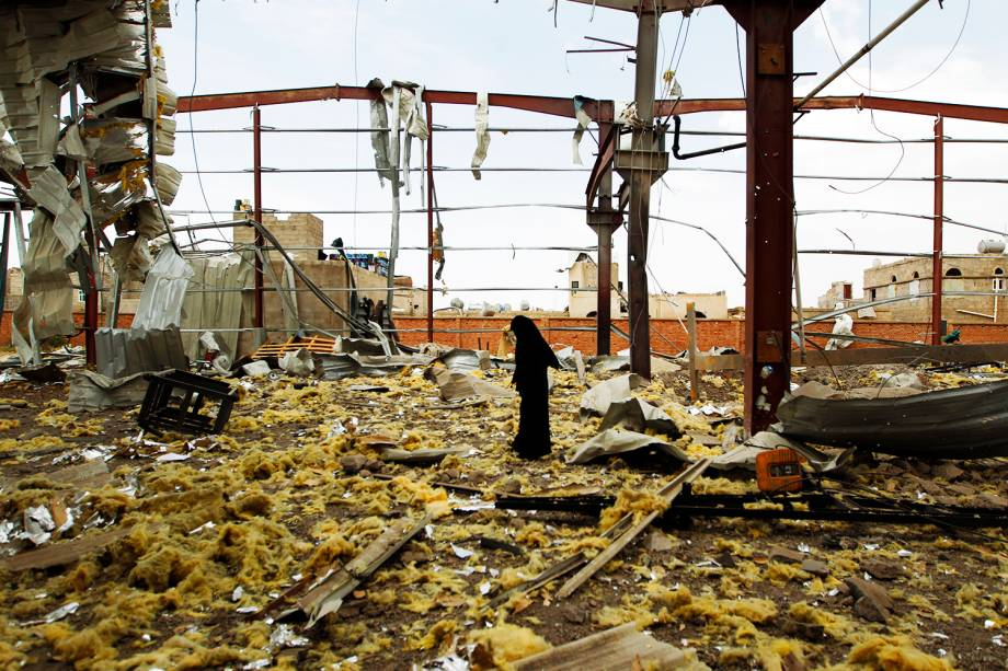 Mulher observa fábrica destruída após ataques aéreos ocorrerem em Saná, no Iêmen - 15/09/2016