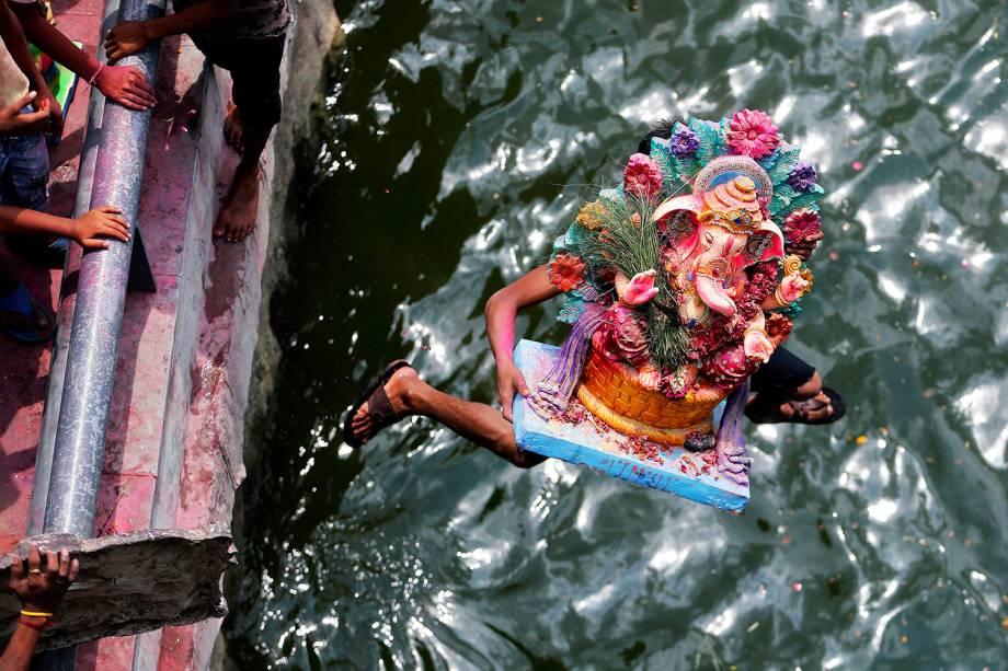 Homem pula no rio Sabarmati carregando imagem do deus Ganesha, durante festival em Ahmedabad, na Índia - 15/09/2016