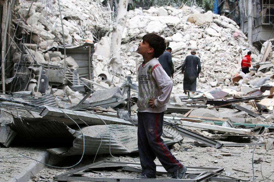 Menino caminha em meio aos destroços de um ataque aéreo em Ansari, distrito de Alepo, na Síria - 23/09/2016