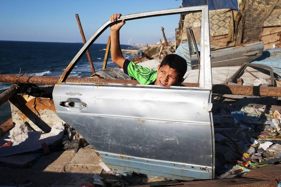 Garoto palestino segura porta de carro encontrada em praia próxima à Cidade de Gaza - 28/09/2016