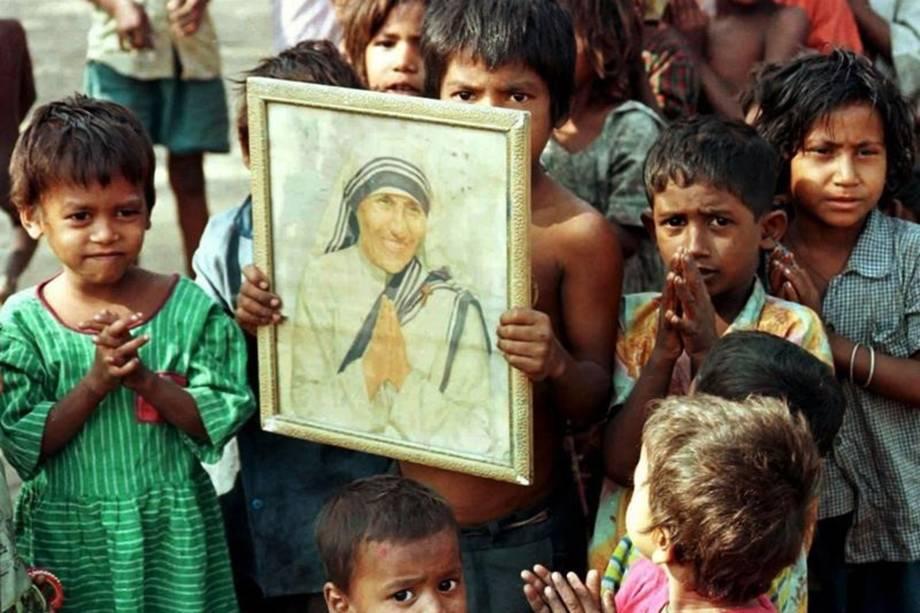 Criança indiana segura retrato de Madre Teresa de Calcutá - 28/11/1996