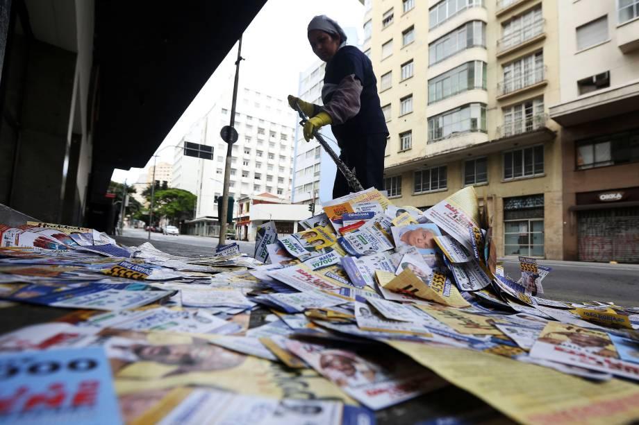 Mulher faz a limpeza de uma calçada repleta de propagandas de candidatos em frente a um edifício no centro de São Paulo - 02/10/2016
