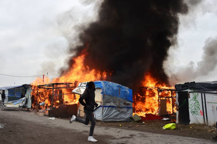 Migrante corre próximo a barracas incendidas no campo de Calais, na França - 26/10/2016
