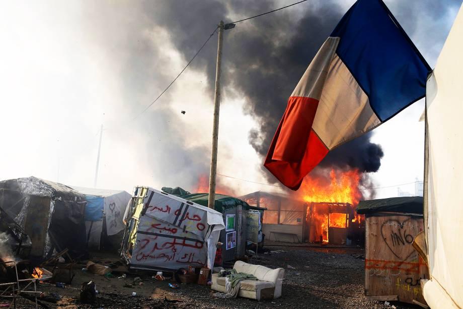 Bandeira francesa é vista no campo de Calais, na França, em meio ao incêndio provocado no local durante o terceiro dia de evacuação de refugiados - 26/10/2016