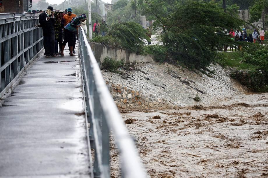 Pessoas observam um rio durante passagem do furacão Matthew por Porto Príncipe, no Haiti - 04-10-2016