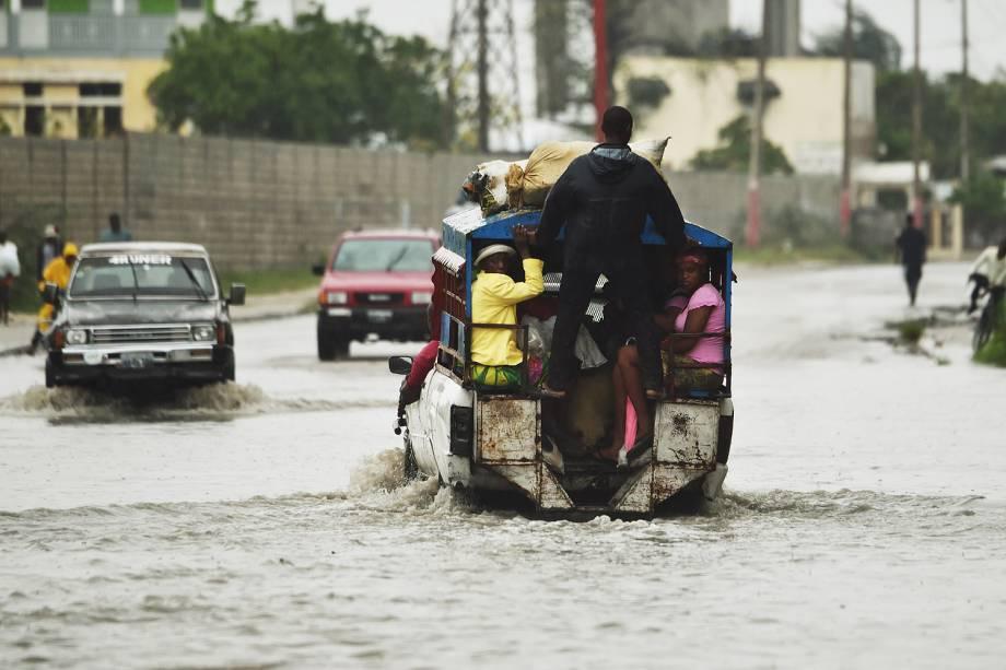 Carros atravessam rua inundada na capital haitiana após as fortes chuvas ocasionadas pelo furacão Matthew - 04-10-2016