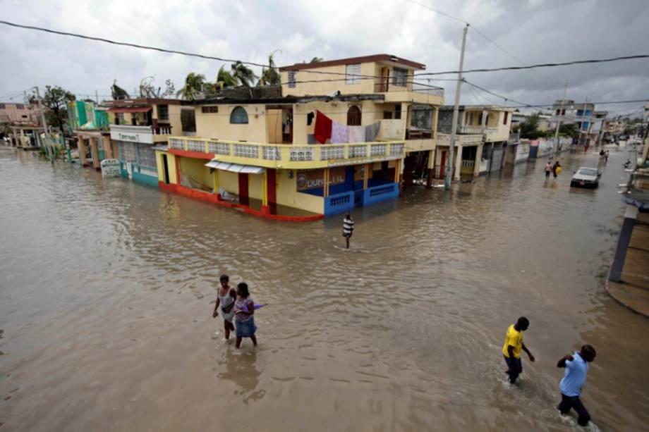 Civis tentam recuperar alguns objetos após a passagem do furacão Matthew, no Haiti