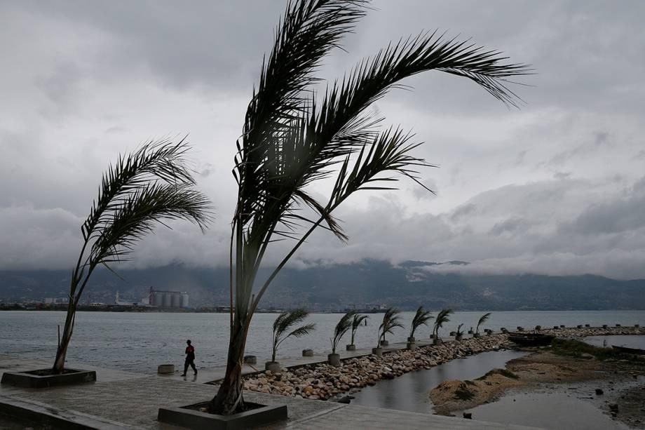Homem caminha no píer de Porto Príncipe, enquanto o furacão Matthew se aproxima da região