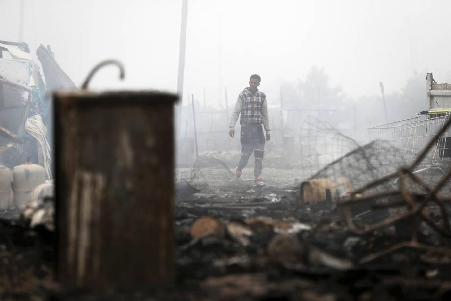 Migrante caminha entre barracas incendiadas no campo de Calais, na França. Evacuação do local já dura três dias. Os refugiados serão levados para centros de acolhimento - 26/10/2016