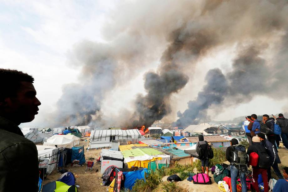 Migrantes observam barracas sendo incendiadas no campo de Calais, na França. Os refugiados serão evacuados e transferidos para centros de acolhimento - 26/10/2016