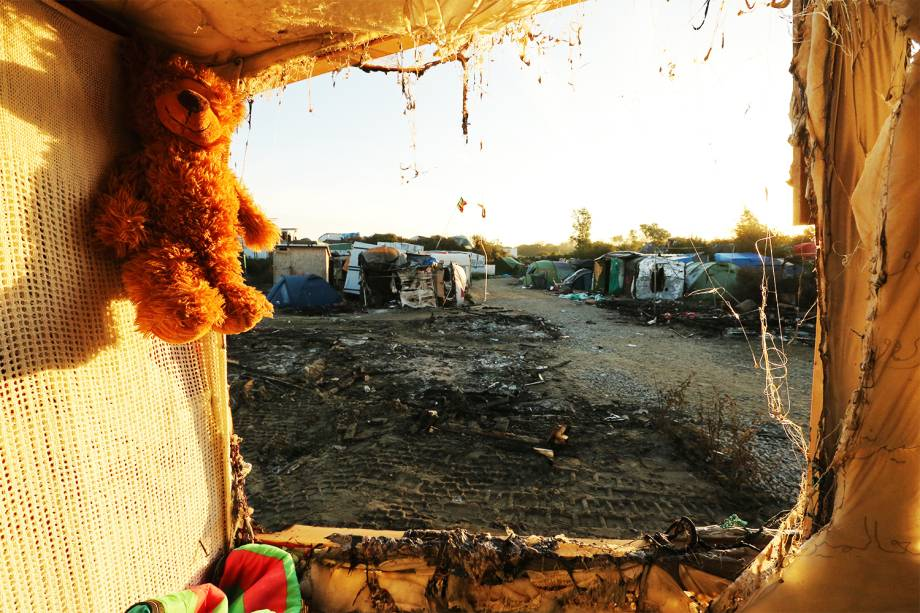 """A teddy bear left behind my migrants hangs at the demolished """"Jungle"""" migrant camp in Calais in northern France on October 28, 2016. Migrants left behind after the demolition of France's notorious """"Jungle"""" faced a day of reckoning after spending the night, with official blessing, in a disused part of the camp. After thousands were bussed out over the past two days, the camp next to the northern port of Calais was virtually deserted. But scores of lost souls were still looking for shelter -- or refusing to leave the squalid settlement that has become one of the most visible symbols of Europe's migrant crisis. / AFP PHOTO / FranÁois NASCIMBENI"""