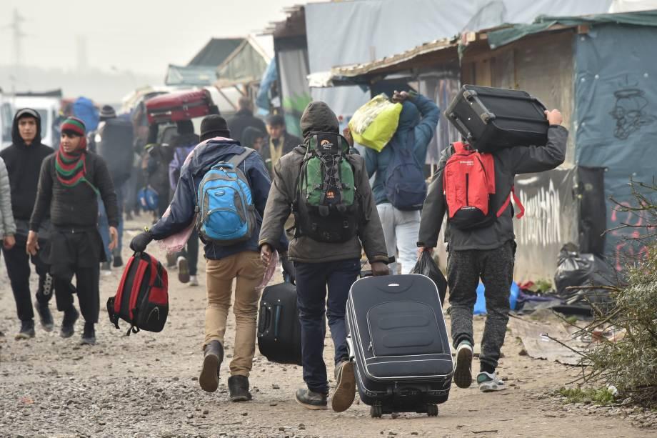 Imigrantes caminham com suas malas em direção a um ponto de encontro definido pelas autoridades francesas como parte da evacuação completa do campo de Calais - 24/10/2016
