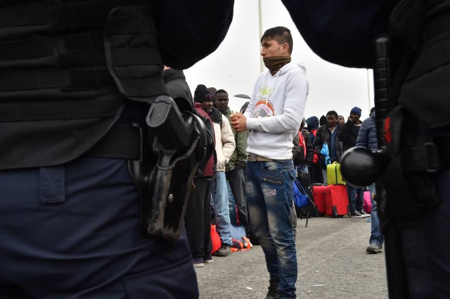 Oficiais da polícia ficam de guarda enquanto imigrantes são conduzidos para deixar o acampamento de Calais, na França - 24/10/2016