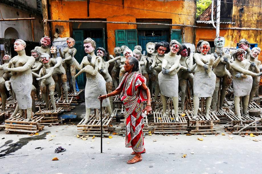Mulher caminha próxima a estátuas inacabadas durante o Festival Kali Puja, em Calcuta, na Índia - 24/10/2016