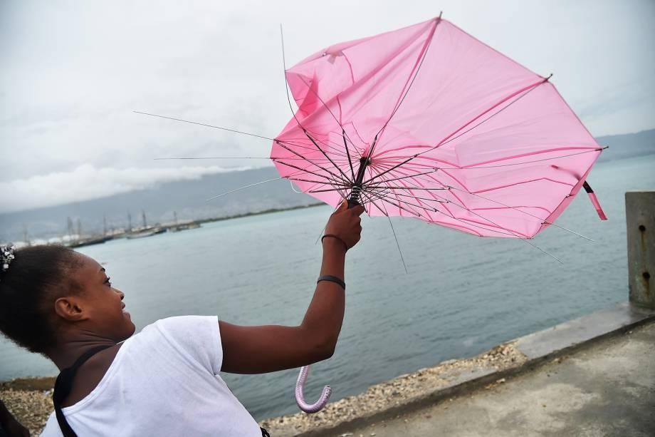 Garota tenta consertar seu guarda-chuva, que foi quebrado pelo vento durante a possível chegada do furacão Matthew, na capital do Haiti Port-au-Prince - 03-10-2016