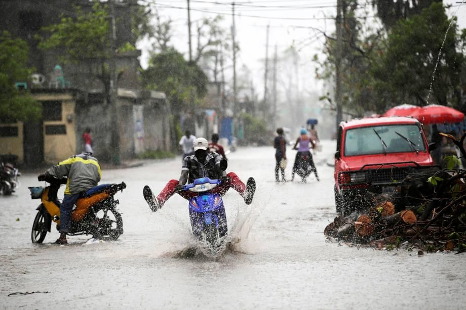 Homem dirige motocicleta após grande tempestade atingir a cidade de Les Cayes, no Haiti - 18/10/2016
