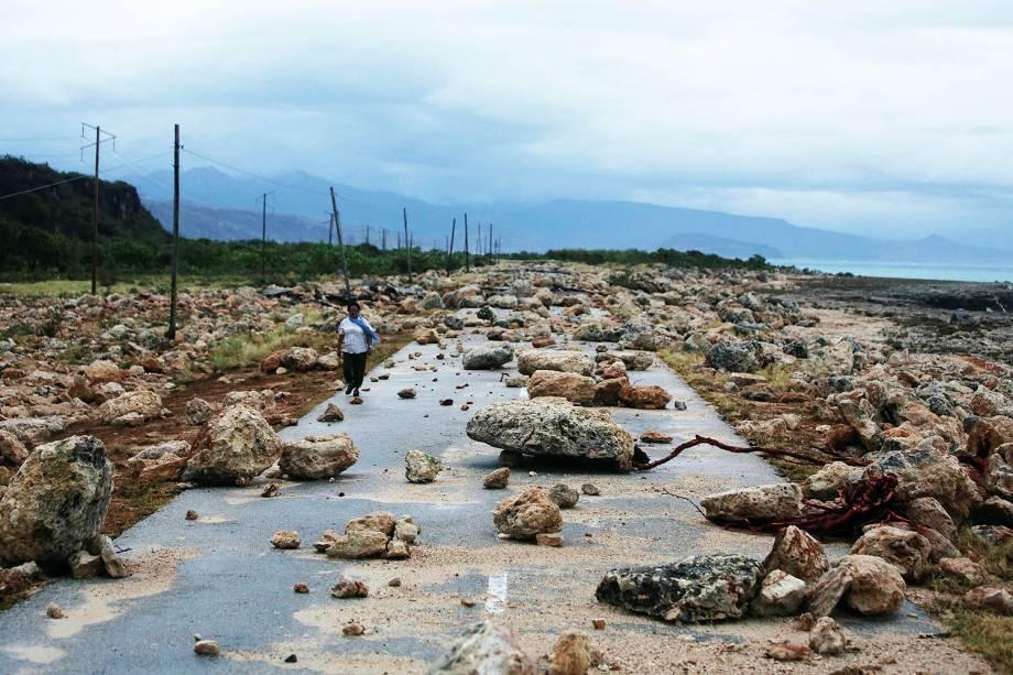 Mulher é fotografada em uma rodovia entre rochas que foram arrastadas pela água devido à passagem do furacão Matthew na costa da província de Guantânamo, em Cuba - 05-10-2016