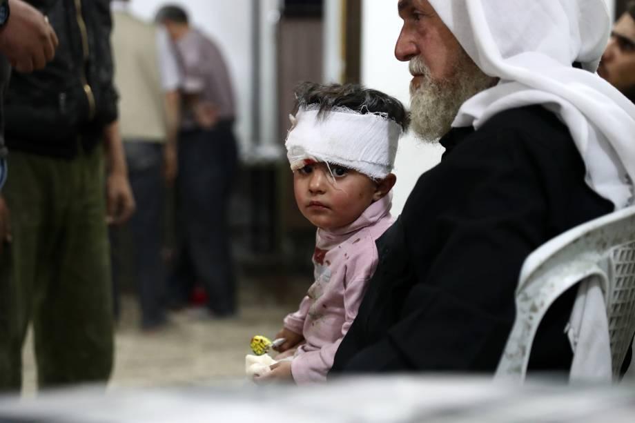 Criança ferida espera após receber tratamento em um hospital improvisado na sequência de ataques aéreos na cidade controlada pelos rebeldes de Douma, periferia de Damasco, na Síria - 03/10/2016