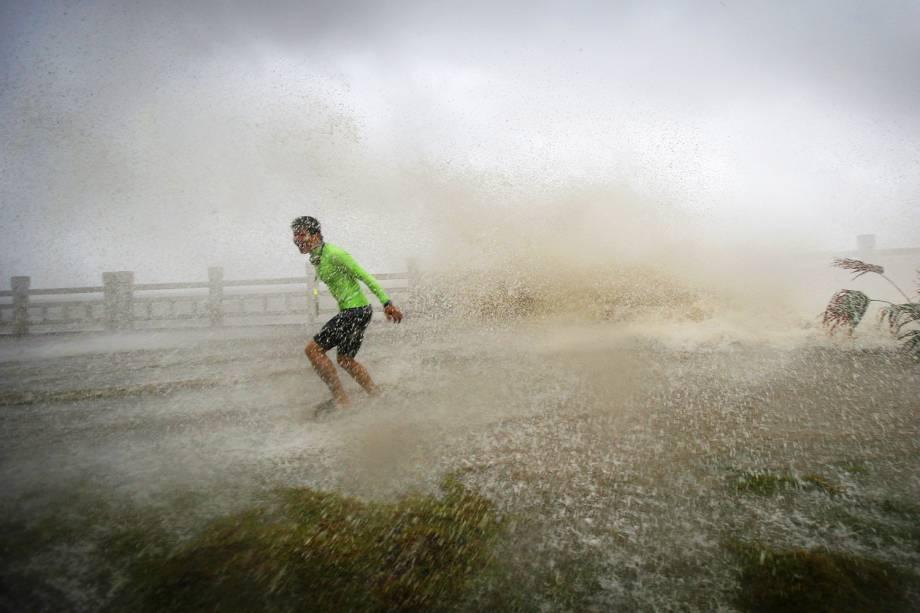 Homem se diverte com ondas em uma praia, na província chinesa de Hainan - 18/10/2016