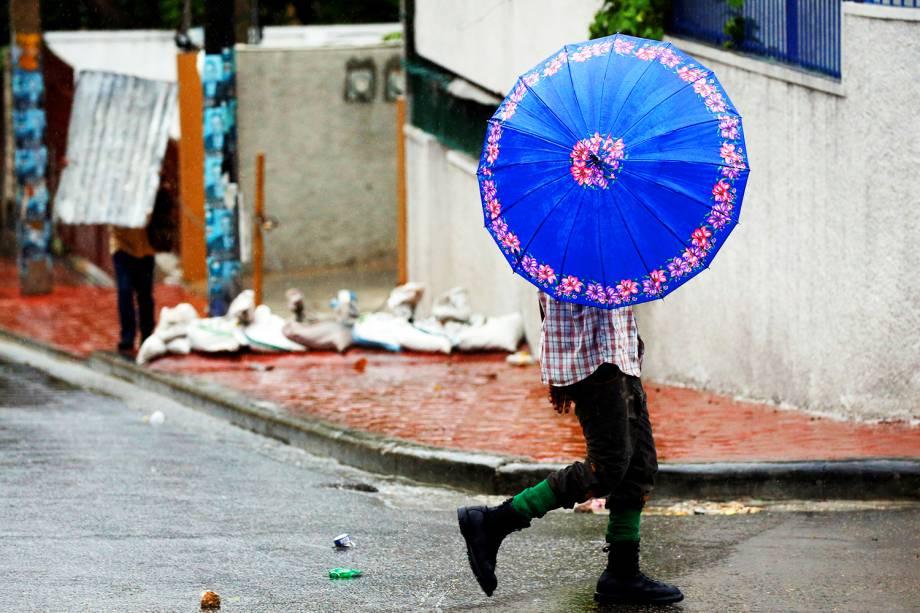 Pedestre se protege de ventania durante a passagem do furacão Matthew em Porto Príncipe, capital do Haiti - 04/10/2016