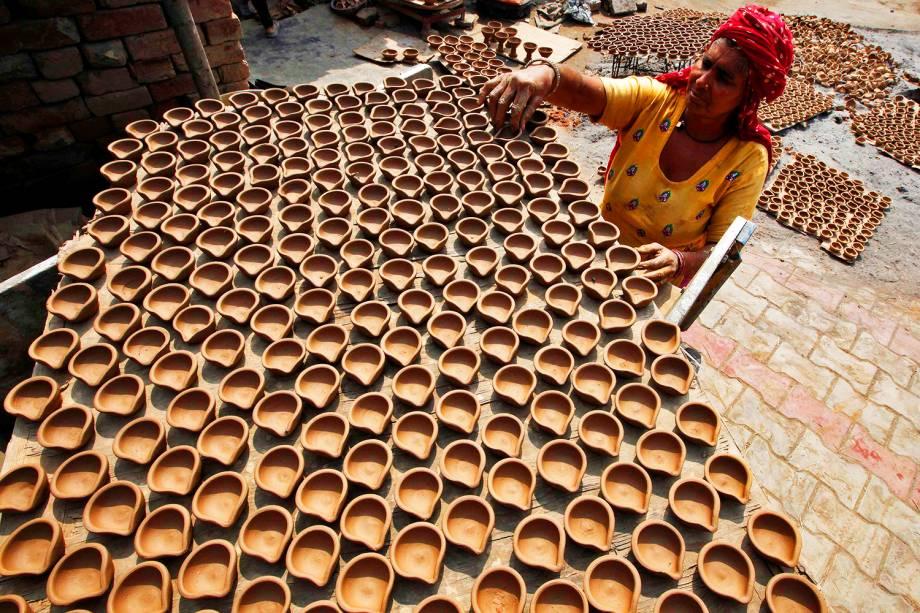 Mulher prepara lâmpadas de barro que serão utilizadas como decoração em residências, no festival religioso de Diwali, na Índia - 07/10/2016