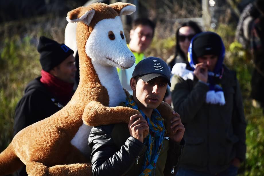 Homem carrega um canguru de pelúcia em suas costas após o esvaziamento do acampamento de refugiados, que ficou conhecido como a 'Selva' de Calais, na França - 28-10-2016