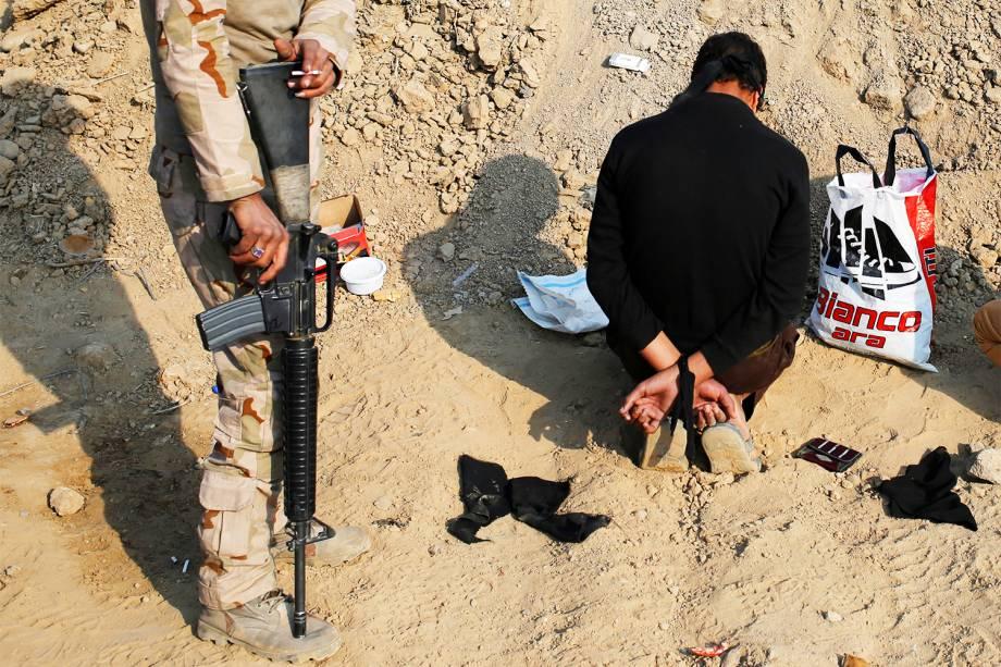 Soldado iraquiano detém suspeito de pertencer ao grupo extremista Estado Islâmico, durante ofensiva militar em Qayyara, no sul de Mosul - 27/10/2016