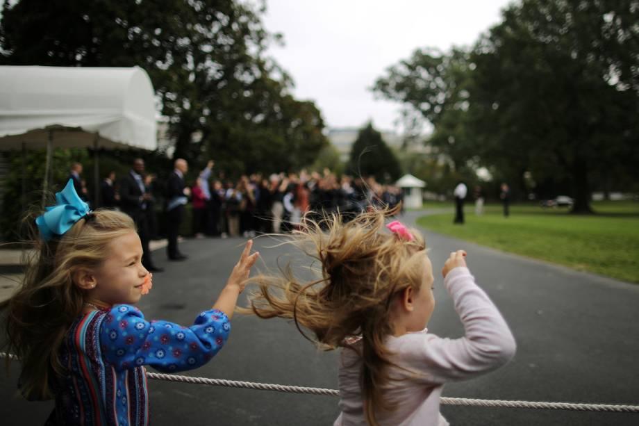 Duas garotas observam e acenam para o presidente Barack Obama, enquanto é escoltado pela marinha norteamericana, em Chicago - 07/10/2016