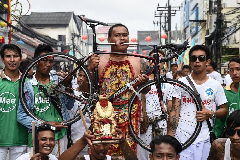 Homem desfila pela rua com o rosto perfurado pelo cano de uma bicicleta durante o Festival Vegetariano na cidade de Phuket, na Tailândia -03/10/2016