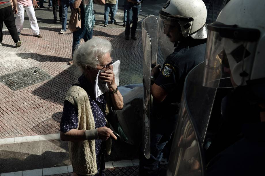 Idosa fica em frente a um bloqueio da polícia durante confrontos em uma manifestação de aposentados contra os cortes de pensão no centro de Atenas, na Grécia - 03/10/2016