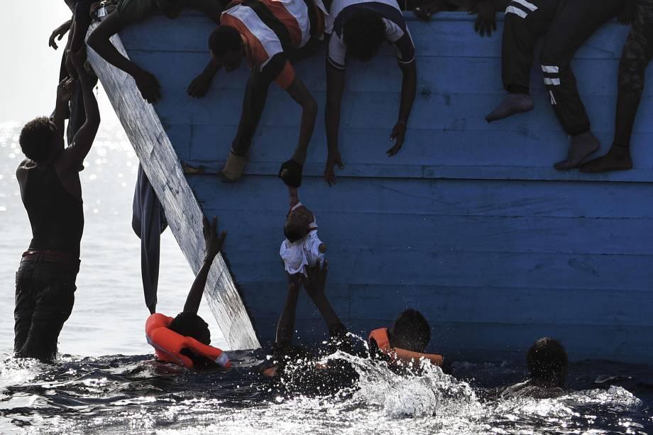 Imigrantes tentam retirar uma criança da água enquanto esperam para ser resgatados pela ONG Proactiva Open Arms no mar Mediterrâneo, ao norte da Líbia - 04/10/2016