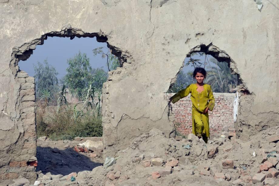 Criança afegã brinca entre os escombros de uma casa em um acampamentos de refugiados em Peshawar, no Paquistão - 24/10/2016