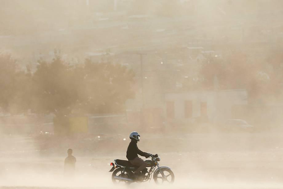 Homem dirige uma motocicleta em meio a uma tempestade de areia em Kabul, no Afeganistão - 18/10/2016