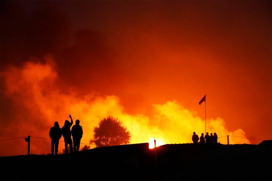 Migrantes são vistos próximos a chamas, durante o segundo dia de evacuação do acampamento localizado em Calais, na França - 25/10/2016