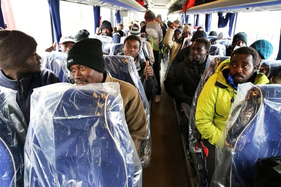 Refugiados são transportados para centros de acolhimento, em ônibus com plásticos cobrindo os assentos, após evacuação do acampamento montado no campo de Calais, na França - 26/10/2016