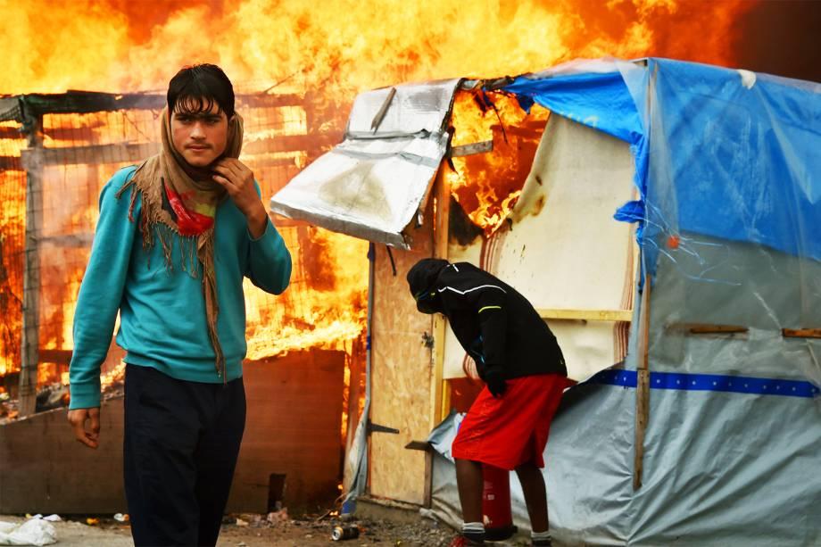 Refugiado observa incêndio em barracas no campo de Calais, na França - 26/10/2016