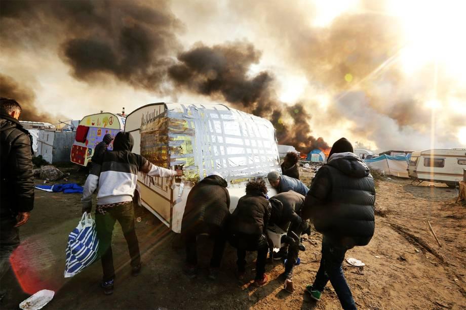 Barracas são incendiadas durante o terceiro dia de evacuação do acampamento montado no campo de Calais - 26/10/2016