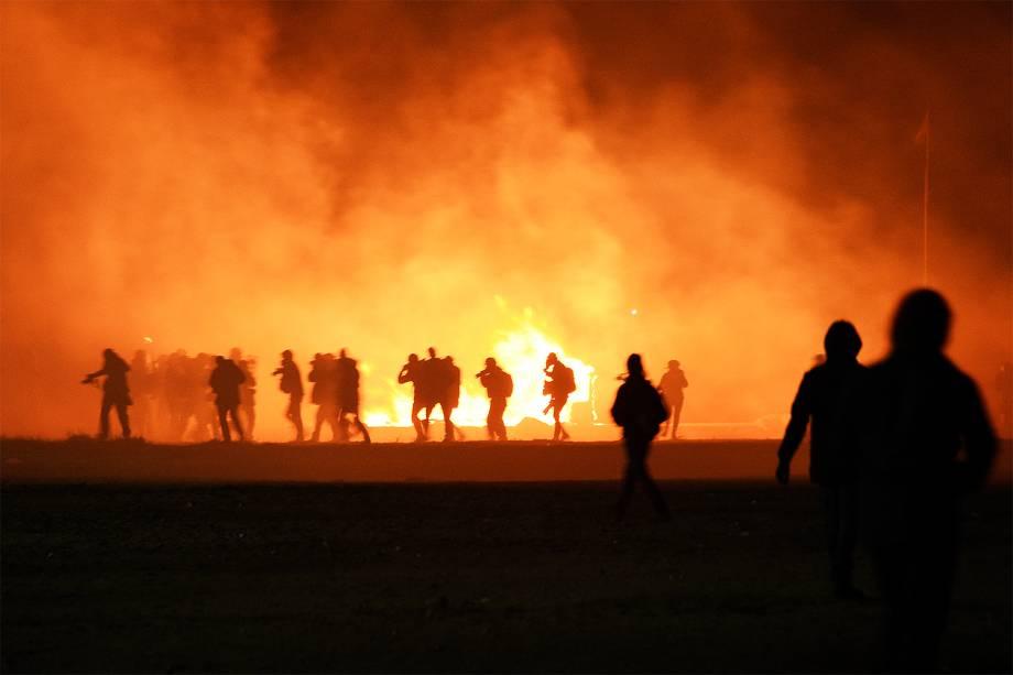 Coluna de fumaça é vista durante a evacuação de migrantes do acampamento localizado em Calais, na França - 23/10/2016
