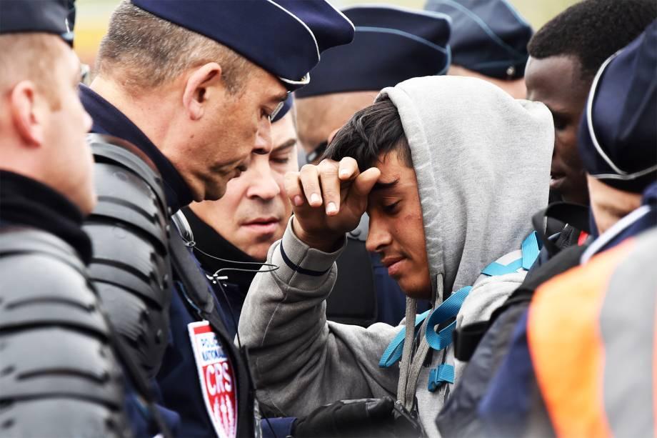Migrante é visto próximo a policiais franceses durante a operação de evacuação do acampamento localizado em Calais - 24/10/2016