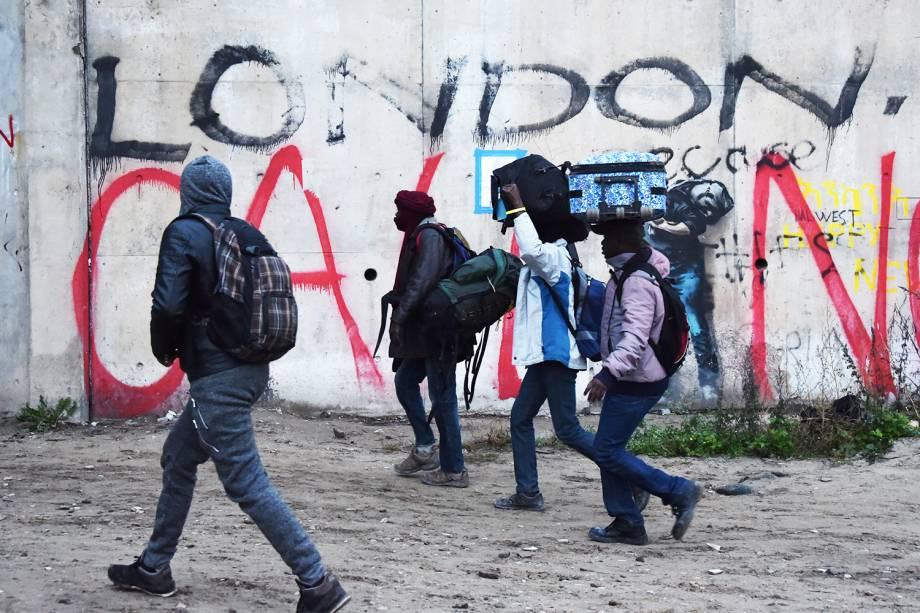Migrantes carregam suas bagagens durante evacuação do acampamento de refugiados localizado em Calais, na França - 24/10/2016