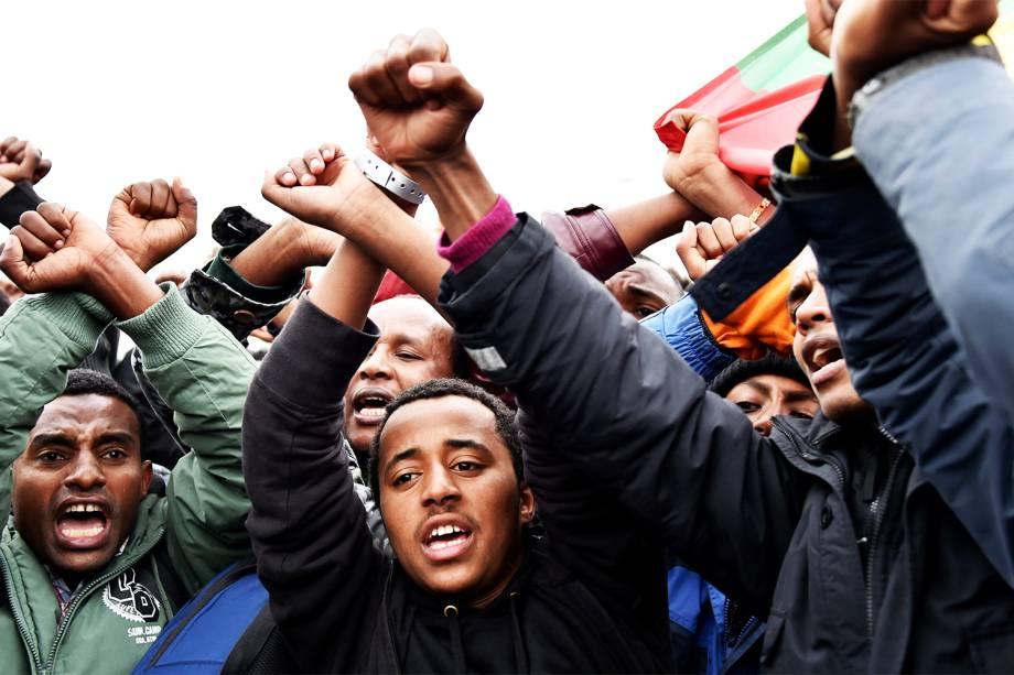 Migrantes da Etiópia cruzam os braços em sinal de protesto durante a evacuação do acampamento de refugiados localizado em Calais, na França - 24/10/2016