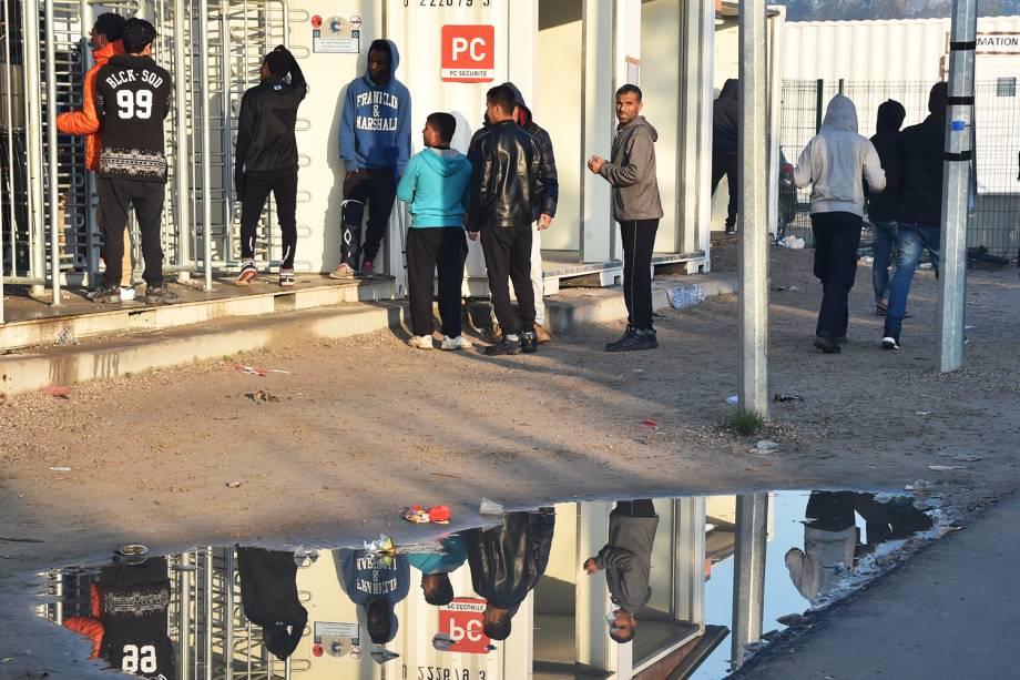 Reflexo de migrantes é visto em uma poça d'água, durante evacuação do acampamento de refugiados localizado em Calais, na França - 25/10/2016