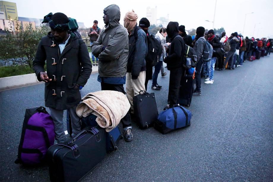 Migrantes fazem fila para serem transportados para centros de acolhimento, durante operação policial para evacuação do acampamento improvisado de refugiados na cidade de Calais, na França - 24/10/2016