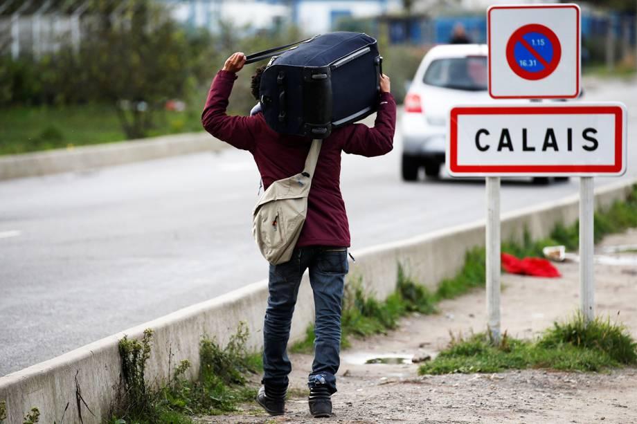 Migrante carrega seus pertences após operação policial no acampamento improvisado de refugiados localizado em Calais, na França - 24/10/2016