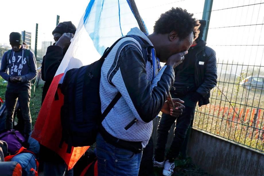 Migrante chora durante o segundo dia de evacuação do acampamento improvisado de refugiados, localizado na cidade de Calais, na França - 25/10/2016